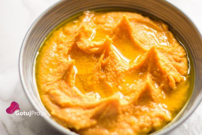 """Hummus z batatów to doskonały dodatek do warzyw, chleba, krakersów czy tapas (małych zakąsek). W oryginalnej wersji wywodzi się z kuchni arabskiej. Na chwilę obecną możemy spotkać wiele różnych odmian hummusu. Hummus z batatów jest jedną z tych odmian i zdecydowanie jedną z najlepszych modyfikacji. Osobiście uwielbiam go używać do kanapek zamiast masła, to taka moja mała przyjemność, która, mam nadzieję, wyjdzie mi na dobre. Doskonale spełnia rolę """"sosu/dipu"""" w daniach wegetariańskich i wegańskich. Wypróbuj również hummus klasyczny."""