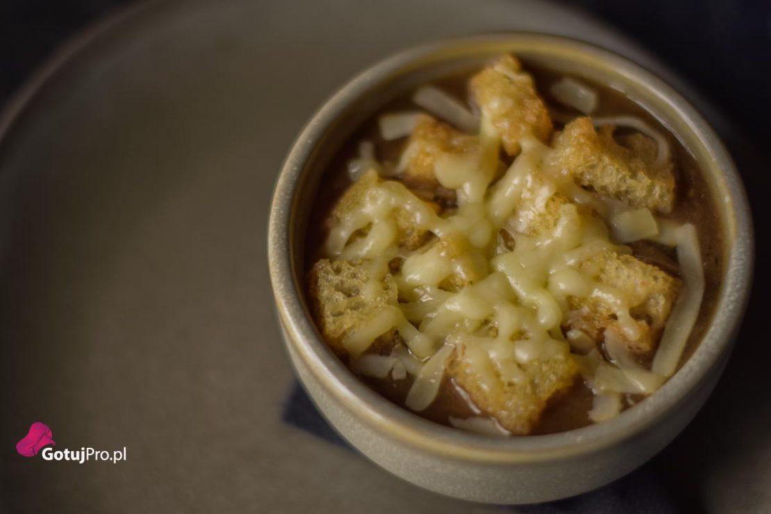 Francuska zupa cebulowa jest przykładem dobrego klasycznego dania prosto z Francuskiego bistro. Tylko garść składników wystarczy aby przygotować jedną z najlepszych zup. Cebula, bulion wołowy, masło, ser gruyère i szczypta soli mieszają się powoli w luksusowej misce z jedwabistą cebulką i ciemnym rosołem. Jeśli jadłeś francuską zupę cebulową tylko w restauracjach, będziesz naprawdę wstrząśnięty tym, jak łatwo jest przygotować w domowej kuchni. Oto przepis krok po kroku jak przygotować najlepszą zupę cebulową, jaką kiedykolwiek jadłeś/aś. Jest to jedna z najprostszych, ale też jedna z najbardziej satysfakcjonujących zup oraz jedyna, którą warto nauczyć się na pamięć, gdzie kluczowym składnikiem jest czas.