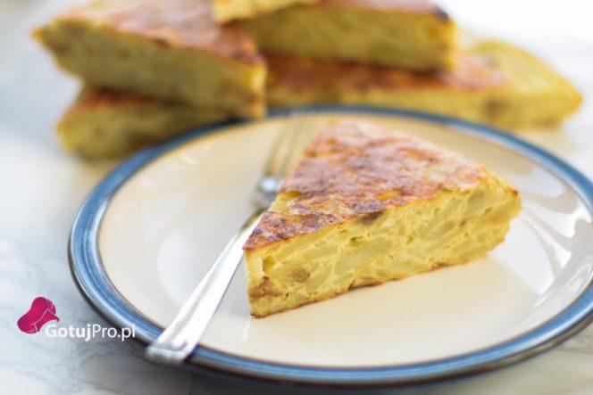 Tortilla Hiszpańska lub Omlet Hiszpański, to klasyczne hiszpańskie danie, które można zjeść na ciepło lub na zimno. Może być podawane jako przystawka lub jako danie główne. Możesz podawać z sałatką i jajkiem w koszulce. Tak naprawdę zastosowań dla Tortilli Hiszpańskiej jest całe mnóstwo. Moim zdaniemTortilla Hiszpańska bardzo dobrze komponuje się z wędzoną rybą i szpinakiem. Tortilla Hiszpańską można przygotować na dwa różne sposoby. Można by powiedzieć, że jedna z nich jest metodą na lenia, natomiast ta druga jest tą metodą właściwą, klasyczną. Rożnica polega w przygotowaniu ziemniaków. W metodzie na lenia gotujemy ziemniaki, kroimy w cienkie plastry. Mieszamy z jakiem, poddajemy obróbce termicznej i po krzyku. Natomiast w metodzie klasycznej, smażymy ziemniaki na patelni. Oczywiście zajmuje to o wiele więcej czasu i trzeba uzbroić się w cierpliwość, ale warto. Przygotowana w ten sposóbTortilla Hiszpańska ma o stokroć lepsze walory smakowe i wspaniałą teksturę dzięki lekko chrupiącym ziemniakom, która sprawia, że jedzenie jej nie jest nudne. W przepisie poniżej możesz zastąpić ziemniaki surowe ugotowanymi ziemniakami.Jak zawsze wybór należy do Ciebie. Bądź PRO!